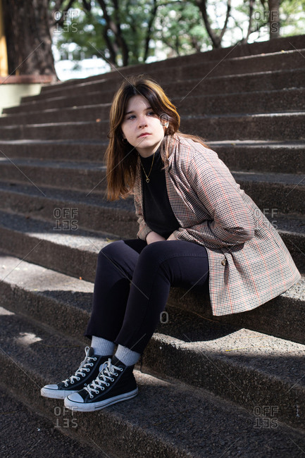 Girl sits on the stone steps of a square in Buenos Aires