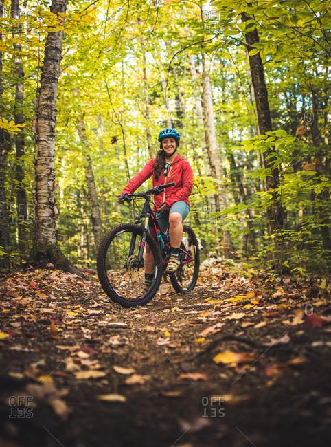 Portrait of female mountain biker standing on trail