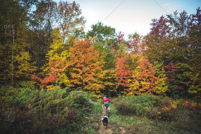 Female mountain-biking downhill with dog behind during foliage season