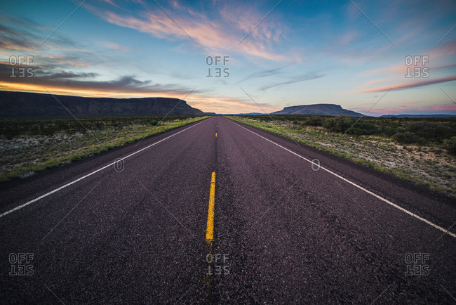 Paved road with yellow stripes in Big Bend National Park during sunset