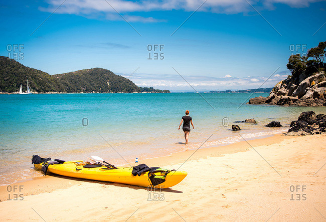 Woman exploring sandy beach with kayak in Abel Tasman National Park
