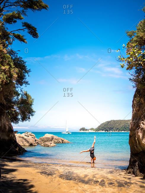 Woman doing a handstand on sandy beach in Abel Tasman National Park
