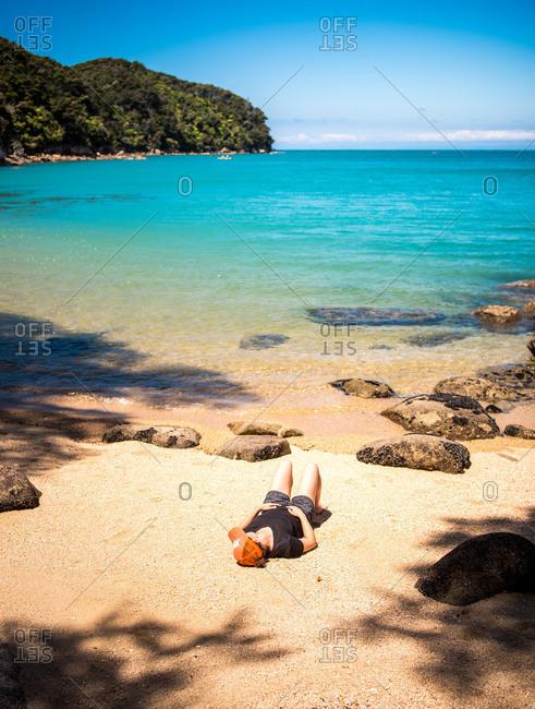 Woman lying on sandy beach in Abel Tasman National Park