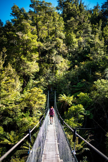 Woman walking across suspension bridge on the Abel Tasman Coast Track