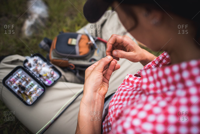 Woman angler ties fly onto end of fly fishing line while sitting