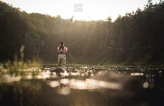 Woman angler fly-fishing in NH backcountry lake with back-lighting
