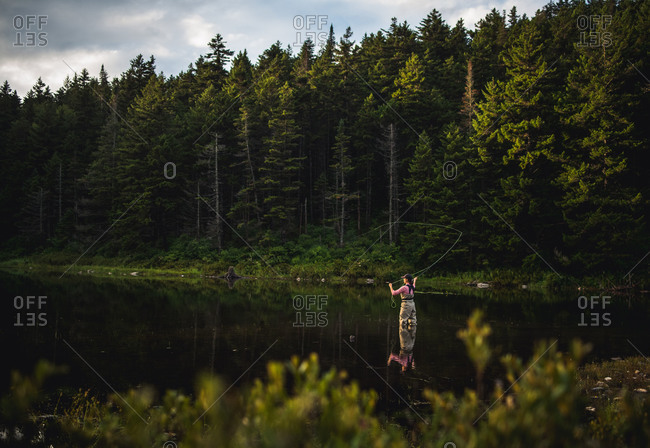 Woman angler fly-fishing in NH backcountry lake during afternoon light