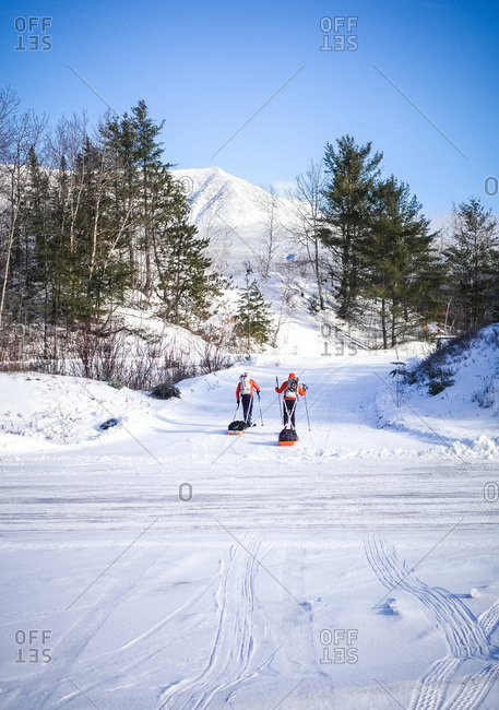 Two men ski across a road dragging pulk sleds in winter