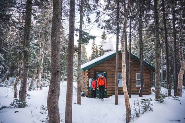 Two men with jackets and backpacks exit a cabin in the a snowy forest