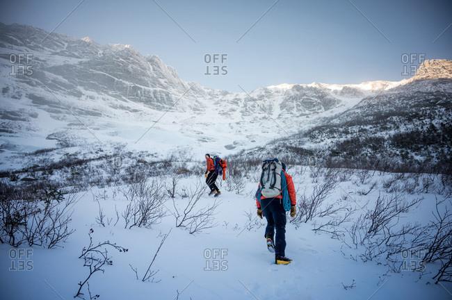 Two male climbers walk upwards towards a mountain ridge in winter