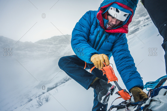 A man puts crampons on during a cold weather alpine ice climb