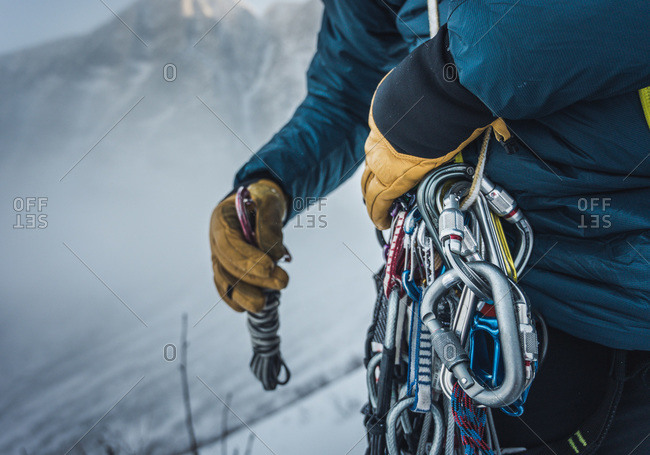 A man sorts through rock and ice climbing gear during a winter climb