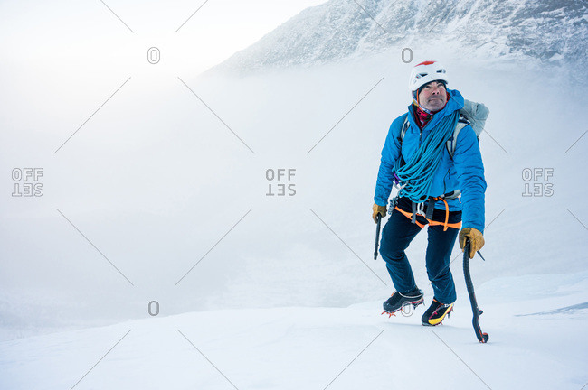 A male alpine climber ascends a steep section of snow with clouds behind