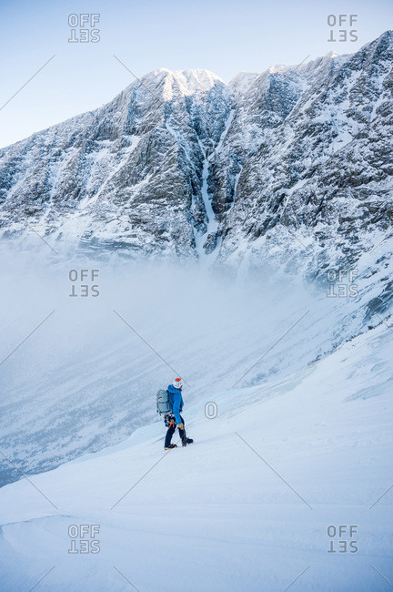 Male alpine climber ascends a steep section of snow, mountains behind