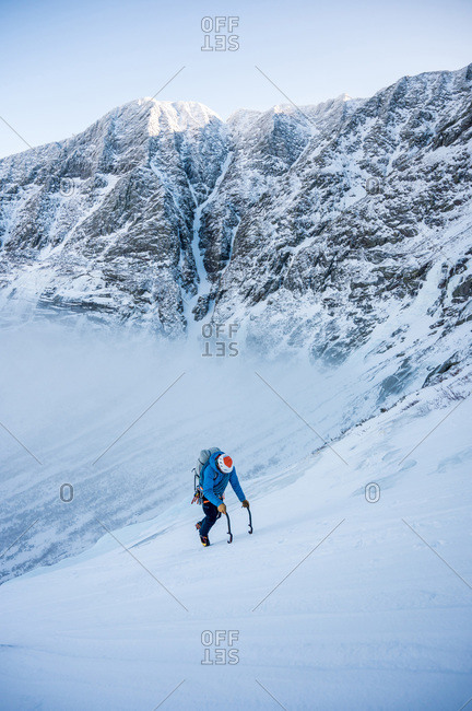 A male alpine climber ascends a steep section of snow with clouds and mountains behind