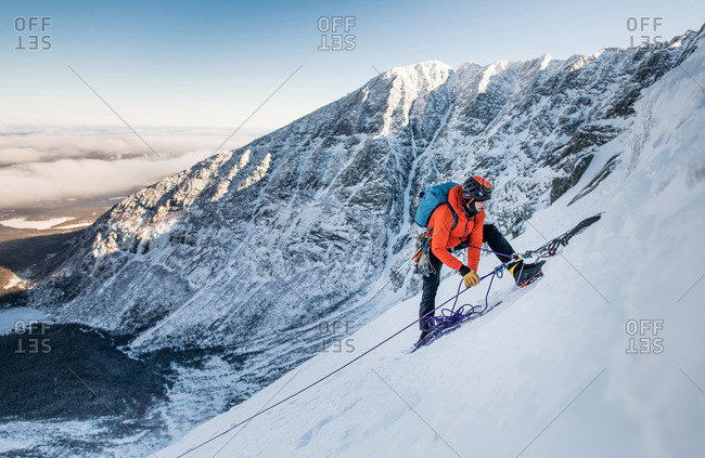 A male climber belays another climber during a winter alpine ice climb