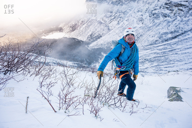 male alpine climber ascends steep section of snow with mountains
