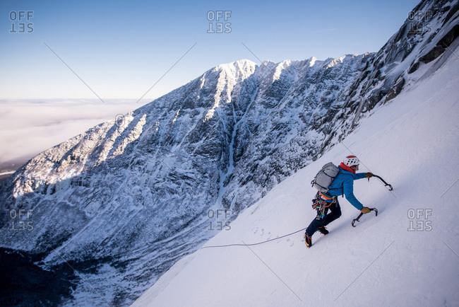 Alpine climber ascending steep snow with mountains behind