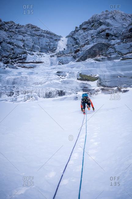 A climber ascends a steep snow section before an ice climb