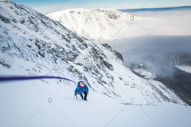 Male climber being belayed up steep snow with cloud inversion behind