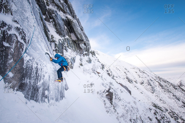 An alpine climber being belayed up a steep section of ice with mountains behind