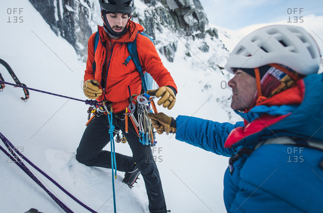 Two male alpine ice climbers sort and exchange ice and rock gear