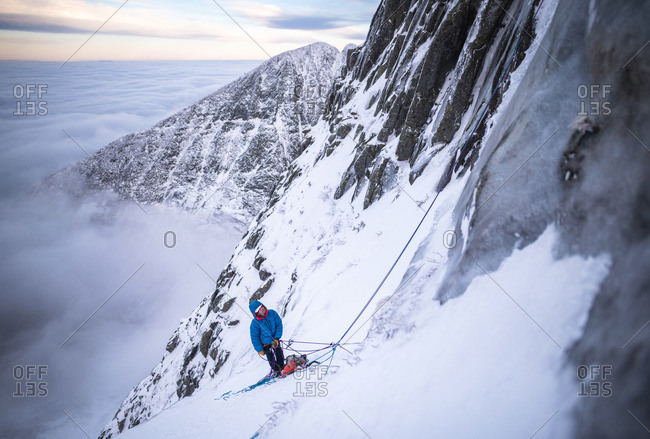 A male climber belaying his lead during a cold winter alpine climb