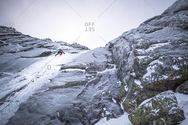 An alpine ice climber climbing a steep section on a large mountain
