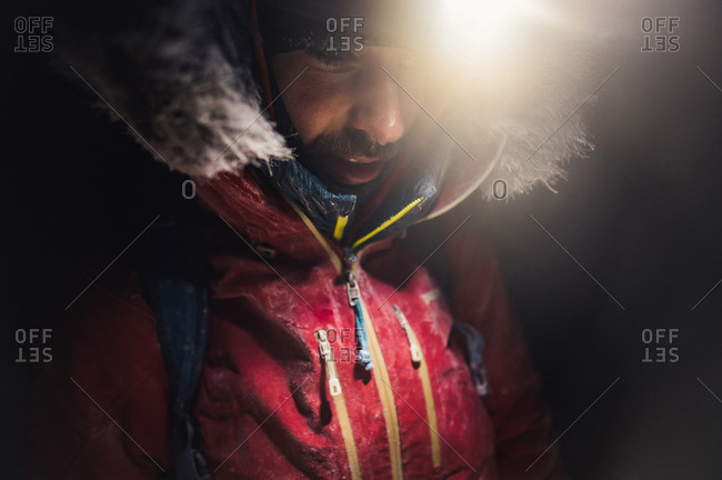 A man with frost and ice on his jacket with headlamp