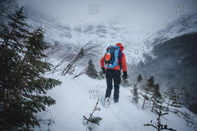 An alpine climber walks through blowing snow while headed to a climb