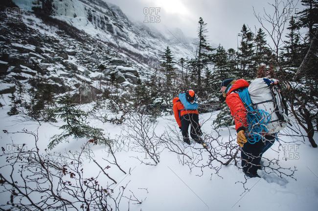 Two alpine climbers walk through deep snow while headed to a climb