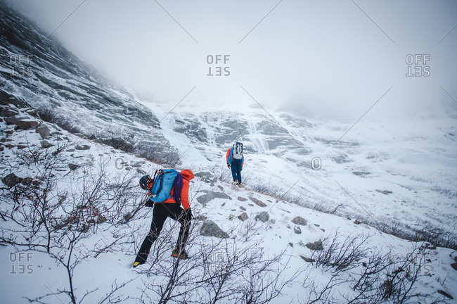 Two alpine climbers walk through blowing snow while headed to a climb