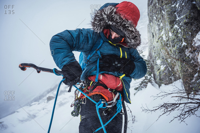 A man clips an ice tool to his harness during a winter ice climb