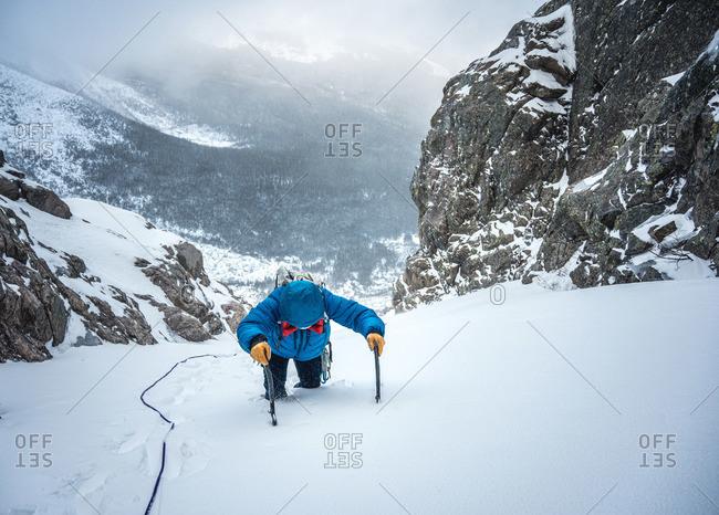 Alpine climber post-holes up a steep section of snow on an ice climb