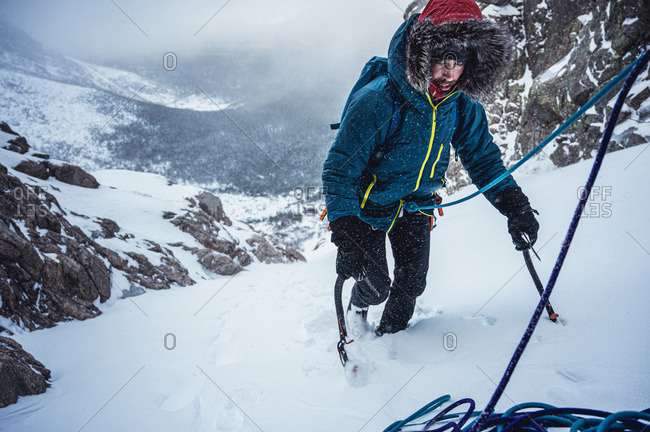 Alpine climber climbs up a steep section of snow
