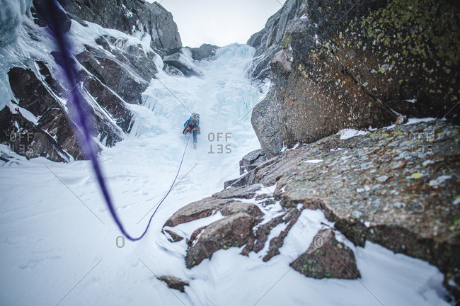 An ice climber climbs up a steep gully full of ice in Maine alpine