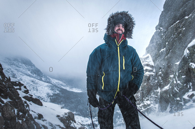 Male alpine climber belays his lead climber as snow blows in the cold