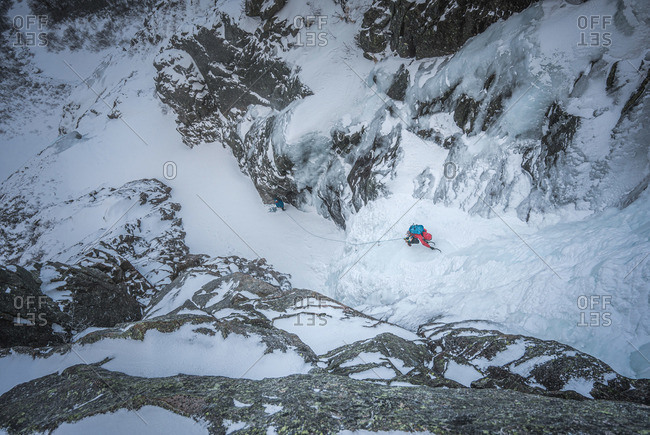 An alpine ice climber ascends a frozen gully in Maine