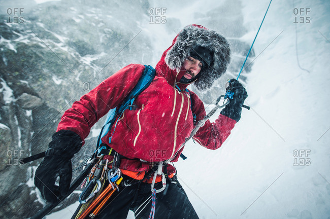 A male ice climber pulls a rope after climbing and rappelling a route