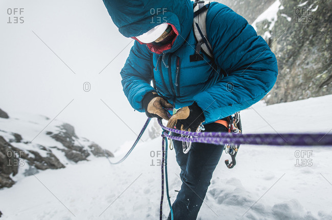 An alpine climber in a puffy jacket puts his belay device on ropes