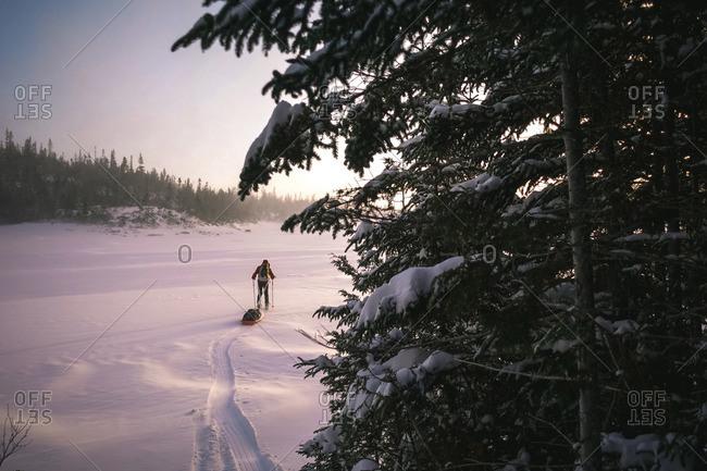 Skier pulling pulk sled walking across a frozen lake at sunrise