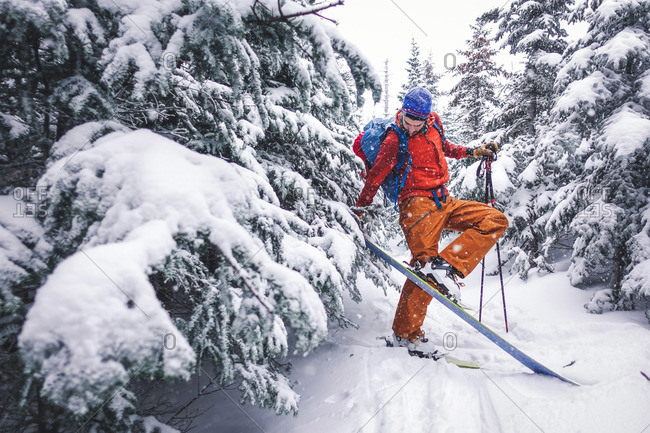 A man removes his skiing skins from his skis during a snowy tour