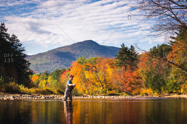 Fly-fisherman casting in river with foliage and reflections