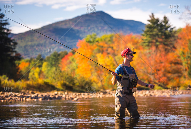 Fly-fisherman casting in river with foliage and mountains