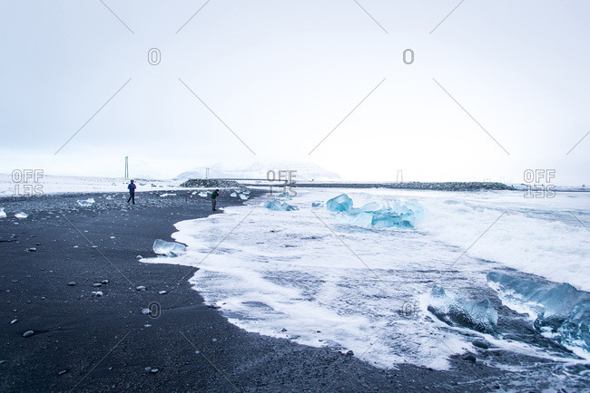 Two people explore black-sand Diamond Beach in Iceland during winter