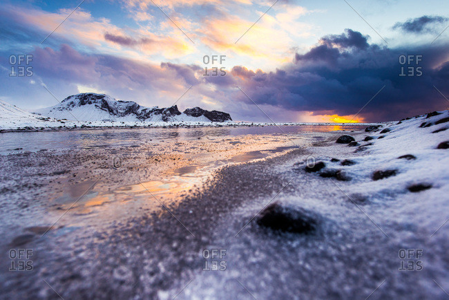 Winter sunrise on the coast of Iceland with mountains in the background