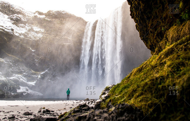 Person standing at Skogafoss waterfall in the winter with moss in foreground