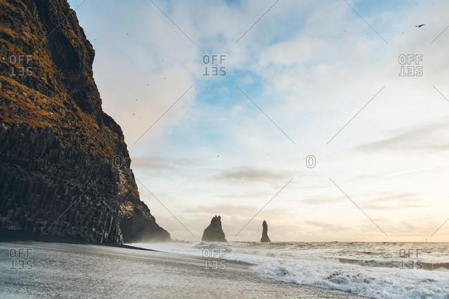 Sea stacks off Reynisfjara black sand beach in Iceland during sunset
