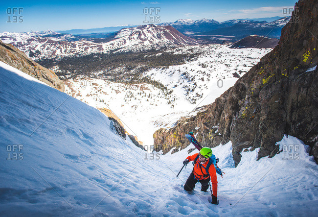 Man with split board on back climbs steep snow gulley