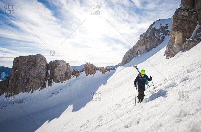 Man walking up steep snow section in California backcountry with skis